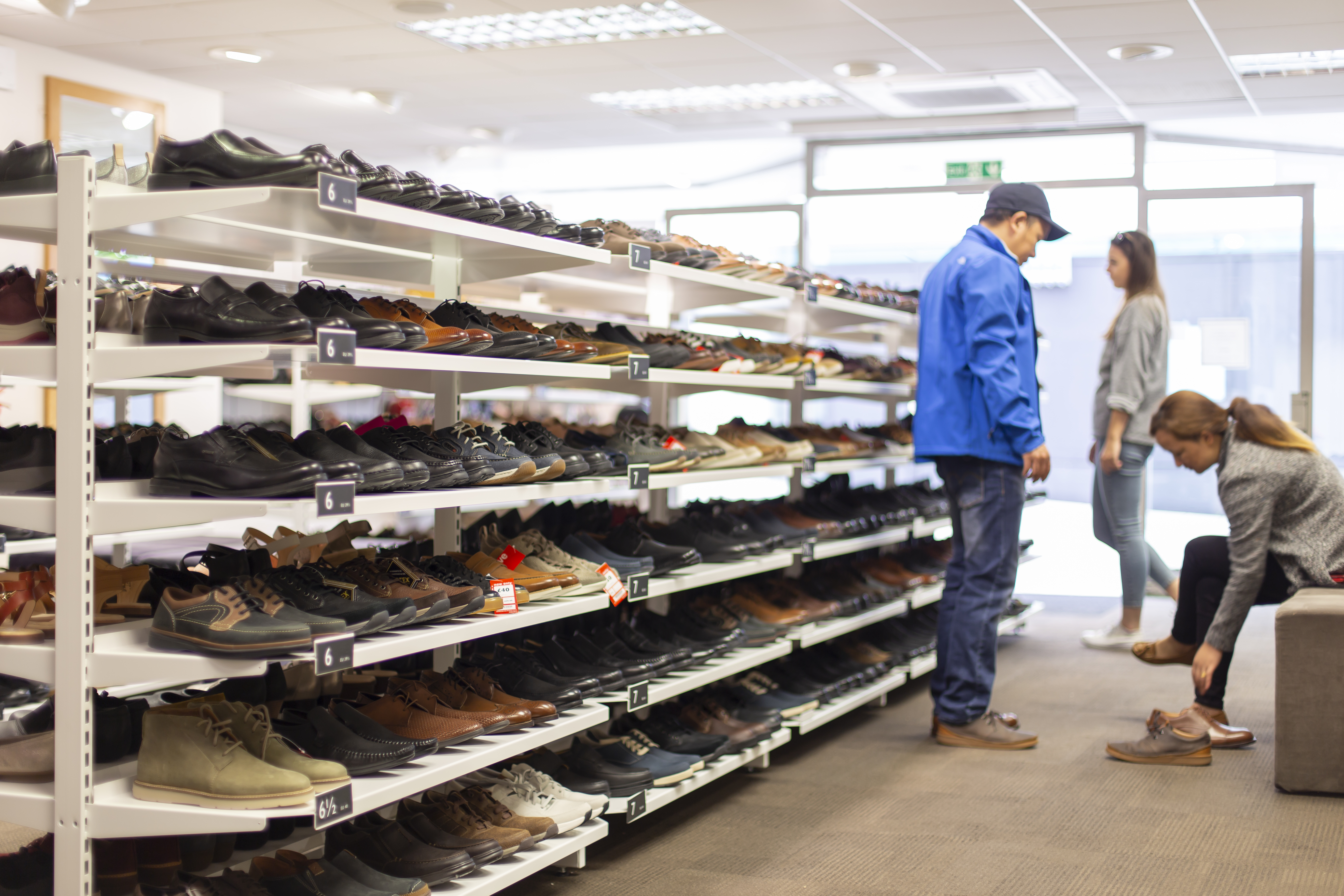 Customers trying on Clarks shoes